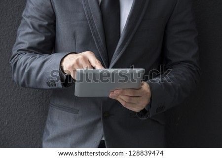 Closeup of a Chinese man with a tablet computer. Asian business man using digital tablet computer, leaning against a black wall.