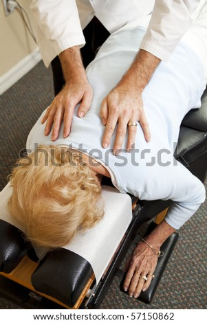 Closeup of a chiropractor's hands as he adjusts a senior patien in his office.