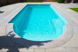 Closeup of a classic private swimmingpool in garden in the summer. with stairs