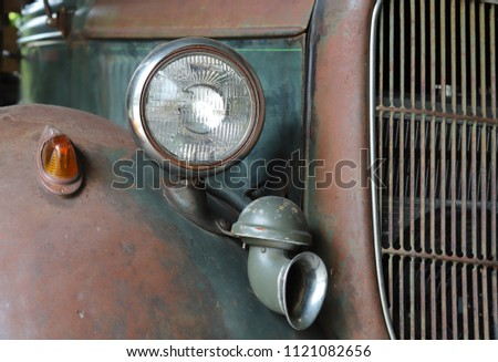 Closeup of a classic right side headlight and horn of vintage car with sunlight. #1121082656