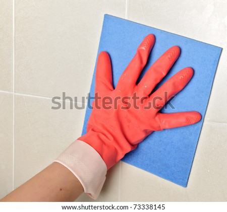 closeup of a cleaning glove and sponge on tiles