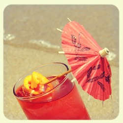 closeup of a cocktail on the sand of a beach, with a retro effect