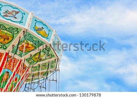 Closeup of a colorful carousel with blue sky background and copy space