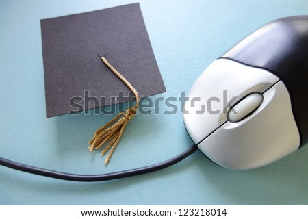 Closeup of a computer mouse and graduation cap - online education concept