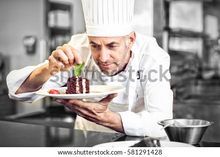 Closeup of a concentrated male pastry chef decorating dessert in the kitchen