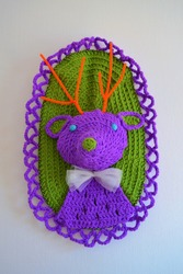 Closeup of a crocheted taxidermy deer in purple and green with a white bow tie hanging on a wall