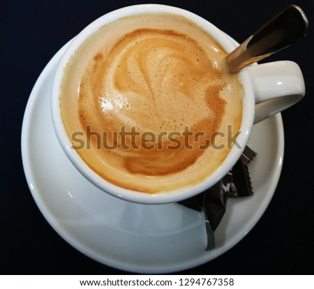 Closeup of a cup of coffee with milk, with white cup and plate a teaspoon and a bon bon.