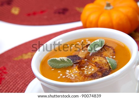 Closeup of a cup of hot delicious spicy roasted pumpkin soup with pumpkin crisps, sage and sesame seeds.