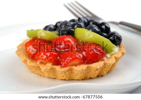Closeup of a delicious custard filled tart topped with fruit.