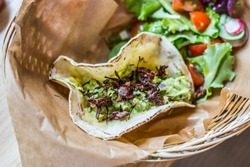 Closeup of a delicious taco with guacamole and chapulines accompanied by a green salad with cherry tomatoes in a wicker basket on a sheet of brown baking paper