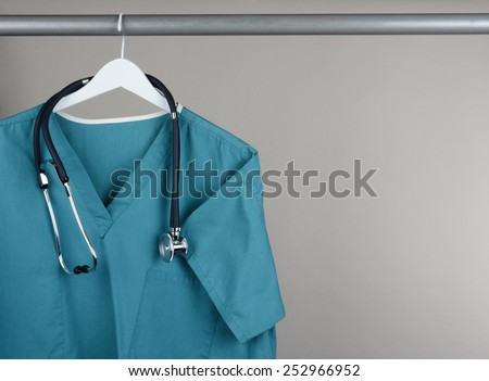 Closeup of a doctor\'s scrubs and stethoscope on hanger against a neutral background. Green surgical smock on a white hanger with a gray background with copy space.