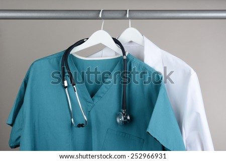 Closeup of a doctor\'s scrubs with stethoscope and lab coat on hangers against a neutral background. Green Scrubs and a white lab coat against a gray background.