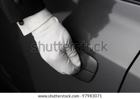 Closeup of a doormans hand on the latch of a car door.
