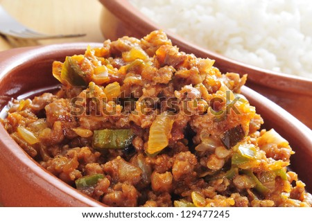 closeup of a earthenware plate with picadillo, a traditional dish in many latin american countries, served with rice