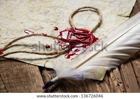 Closeup of a feather and red sealing wax