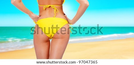 Closeup of a female backside in a yellow swimsuit. A day at a beach concept