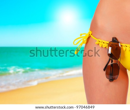 Closeup of a female body in a swimsuit with sunglasses. A day at a beach concept
