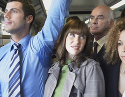Closeup of a female commuter standing by man's wet armpit in a crowded train