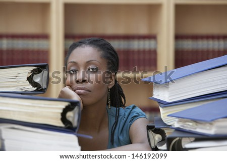 Closeup of a female office worker sitting behind stacks of documents in office