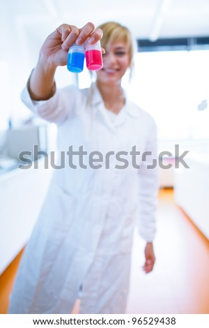 Closeup of a female researcher/chemistry student carrying out experiments in a lab (color toned image)