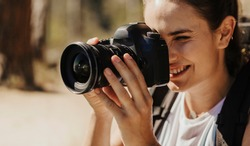 Closeup of a female taking photographs of the landscape with a digital camera. Woman photographer filming scenery with a professional camera.
