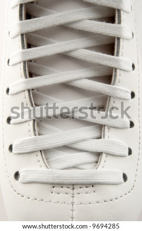 Closeup of a figure skate, showing laces in detail.
