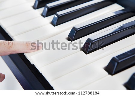 Closeup of a finger playing the piano. shot at studio - stock photo