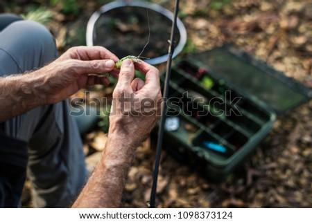 Closeup of a fisherman putting on bait #1098373124