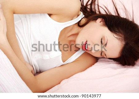 Closeup of a fit and shaped woman having a stomach ache, embracing her belly in bed.