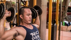 Closeup of a fit Filipino guy doing Seated Dumbbell Shoulder Presses. Training or working out delts.