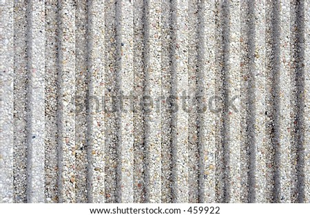 Closeup of a fluted concrete wall for background.  Contains concrete and small stones embedded.  Textured with flutes or grooves.