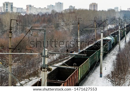 Closeup of a freight train passing through the outskirts of Perm. Most train cars are empty. In the background, multi-storey residential buildings of the city. Winter, December. #1471627553