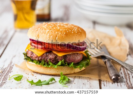 Closeup of a fresh homemade better burger on an old white wooden board with tomato, cheese and red onion.