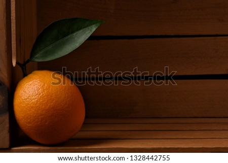 Closeup of a fresh picked navel orange in a wood packing crate. The lone fruit has a stem and leaf and is leaning on the side of the box.