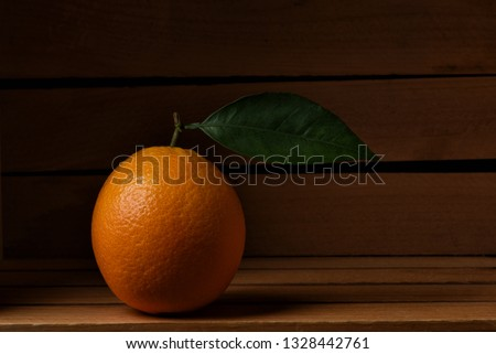Closeup of a fresh picked navel orange in a wood packing crate. The lone fruit has a stem and leaf.