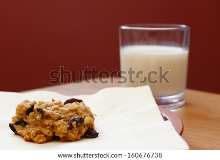 Closeup of a freshly baked oatmeal raisin cookie with a glass of milk