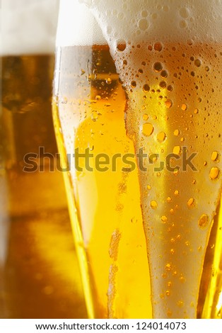 Closeup of a frothy cverflowing glass of golden ale or beer with liquid running down the outside of the glass, cropped view image