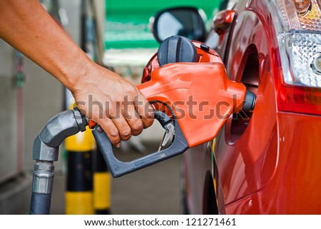 Closeup of a fueling hose at a gas station with a Hand