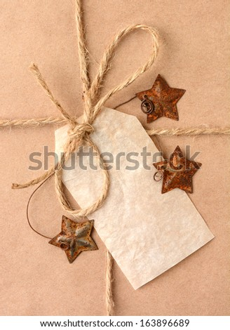 Closeup of a gift tag on a Christmas present. The package is wrapped in plain brown paper with a tied with twine. The package is adorned with metal star shaped ornaments. Vertical Format.