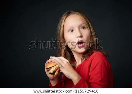 Closeup of a girl holding going to eat a burger looking back over shoulder with a look of surprise  #1155729418