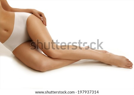 Closeup of a girl lying on the floor showing beautiful legs on white