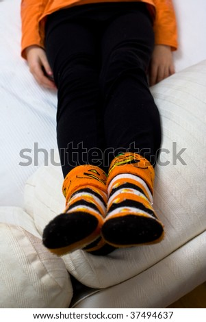 Closeup of a girl's black leggings and Halloween socks, with a pumpkin and candy corn motif. Only her legs and hands are visible, with her feet in focus in the foreground.