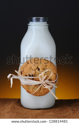 Closeup of a glass milk bottle with two chocolate chip cookies tied to it with rafia. Vertical format with a light to dark warm background.