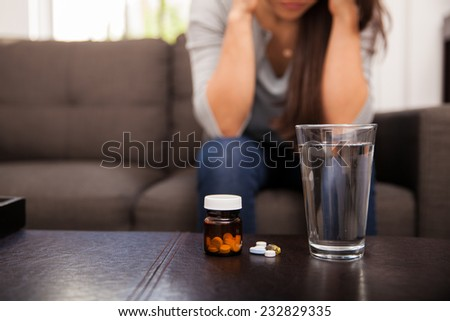 Closeup of a glass of water sitting next to some medicine with a young woman in the background
