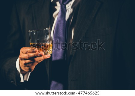 Closeup of a glass of whisky being hold by a business man's hand
