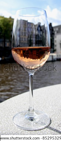 closeup of a glass of wine reflecting the city in the background