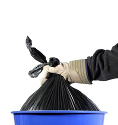 closeup of a gloved hand taking a trash bag out of a blue container
