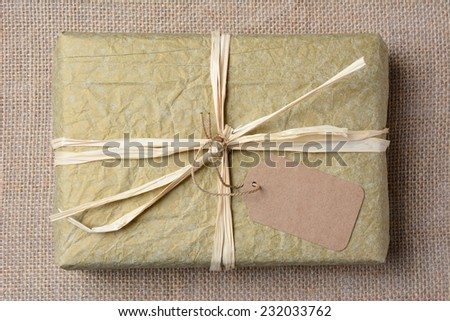 Closeup of a gold tissue paper wrapped present on a burlap surface. The gift is tied with raffia and a blank git tag. High angle shot in horizontal format.