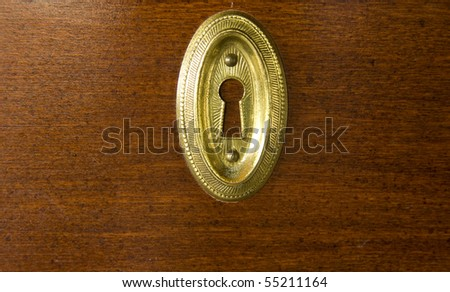 closeup of a golden keyhole on wood background - stock photo
