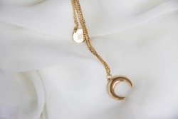 Closeup of a golden necklace with a moon and sun shaped pendant, against a silky white background